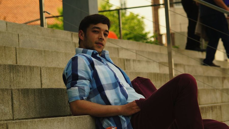 Low angle portrait of man sitting on steps