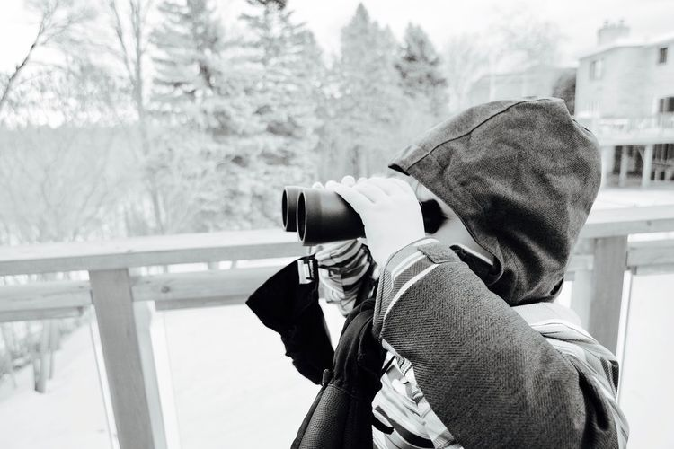 Binoculars Boy Clothing Cold Temperature Day Digital Camera Focus On Foreground Hat Headshot Holding Hood Hood - Clothing Kid Leisure Activity Lifestyles Men One Person Outdoors Real People Rear View Tree Waist Up Warm Clothing Winter