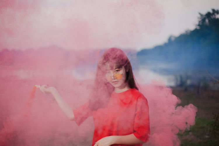 Portrait of young woman holding flaming torch emitting pink smoke