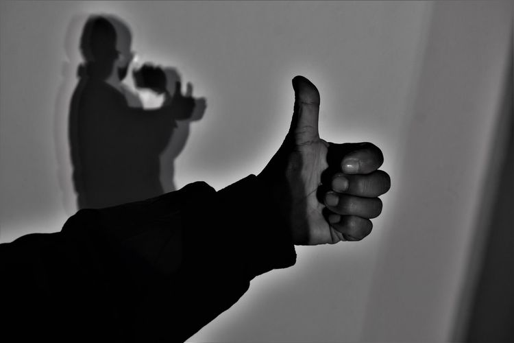 Man standing by shadow gesturing thumbs up at home