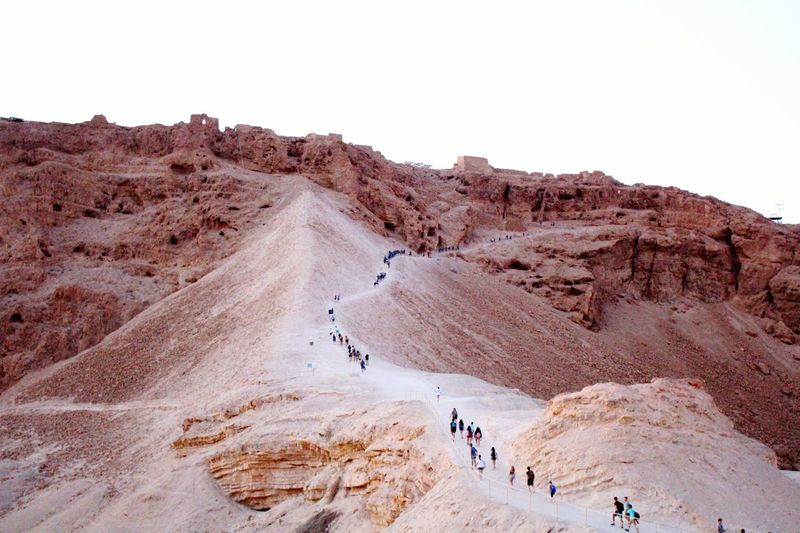 High angle view of people hiking on mountain against clear sky