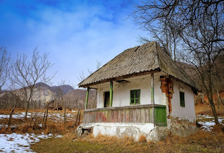 Abandoned House in countryside Grass Traditional House Wooden Fence Abandoned Architecture Bare Tree Building Exterior Built Structure Cold Temperature Country Life Countryside Courtyard  Day Desolate House Mountain Nature No People Outdoors Romanian Traditional House Sky Snow Tree Winter Wooden Porch