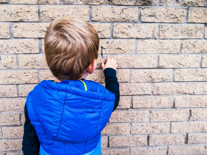 Boy Child Exploring Learning Feeling Texture Kid Wall Brick Natural Light Portrait Urban Building Structure Hoody Jacket Body Warmer Hood Hair Blonde Caucasian Real People Hand From Behind People And Places Beautifully Organized