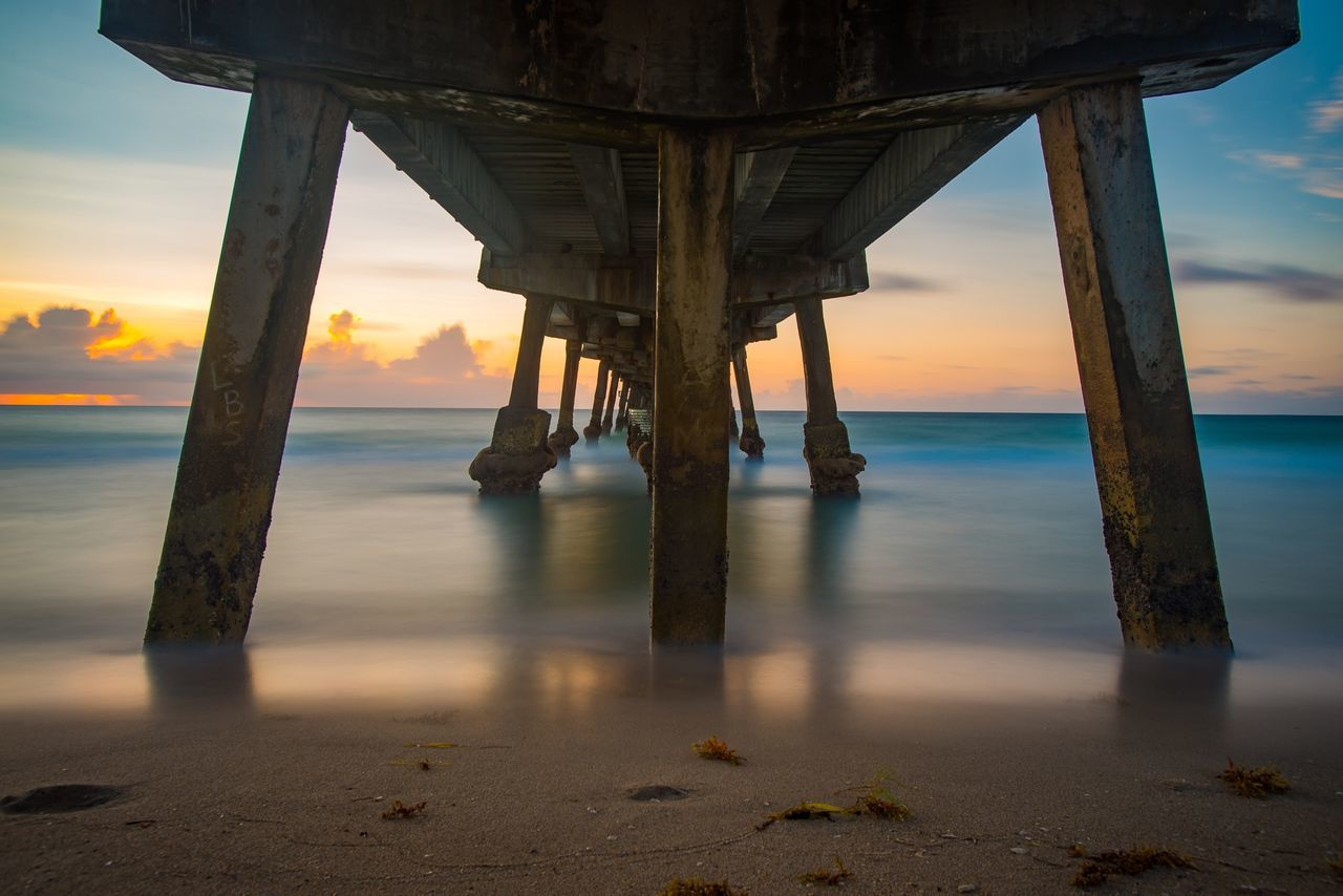 Underneath View Of Pier Over Sea During Sunset