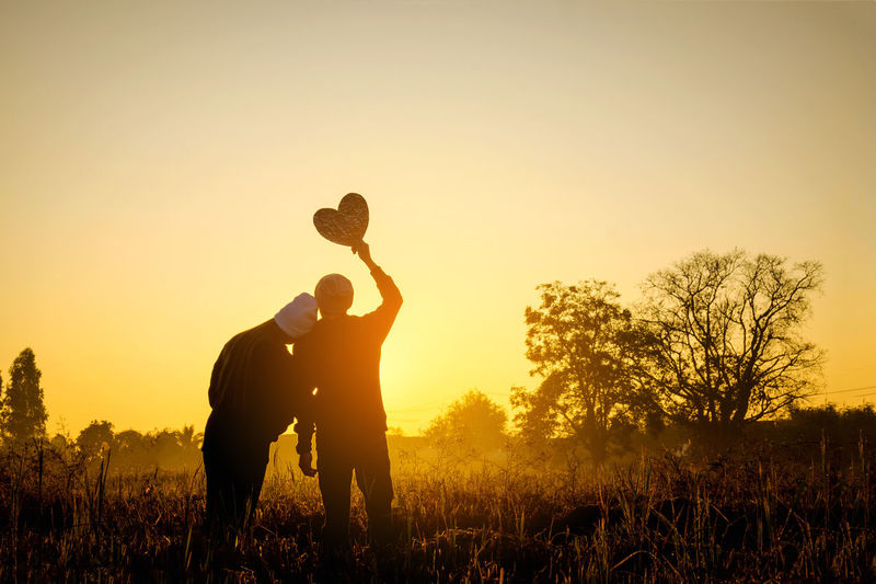 Couple Love Arms Raised Child Field Full Length Holding Land Leisure Activity Lens Flare Lifestyles Men Nature Orange Color Outdoors People Plant Real People Silhouette Sky Standing Sunlight Sunset Togetherness Tree