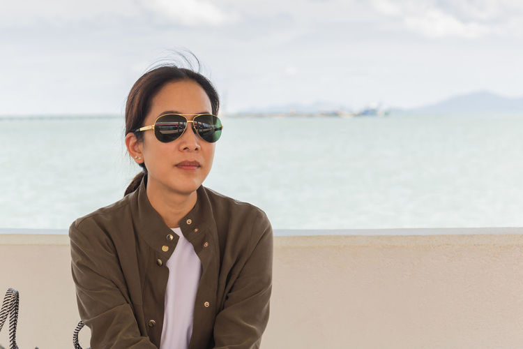 Portrait of man wearing sunglasses standing at beach