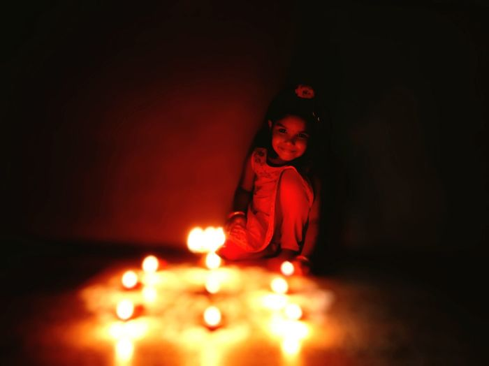 Smiling Girl Looking At Illuminated Decoration In Darkroom