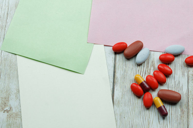 Medication with colorful blank paper on wooden background Medical Medicine Medication Paper Wooden Background Wooden Copy Space Copyspace Tablet Pill Capsule Background Red Wood - Material Variation Close-up Nutritional Supplement Dose Vitamin