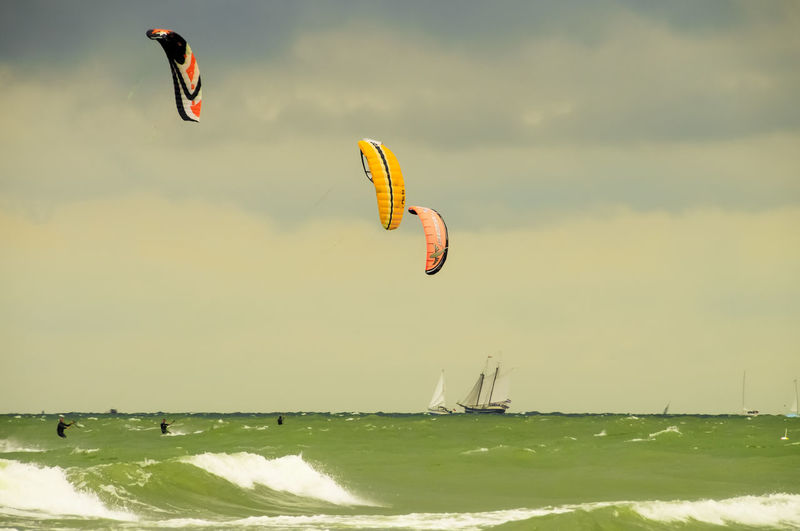 Person paragliding flying over sea against sky