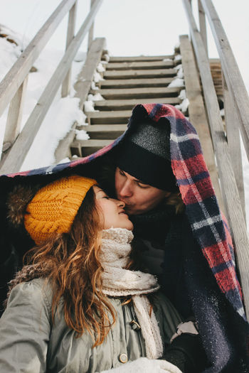Couple in warm clothing kissing on steps