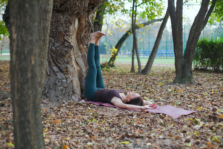 Young woman lying down on tree trunk during autumn