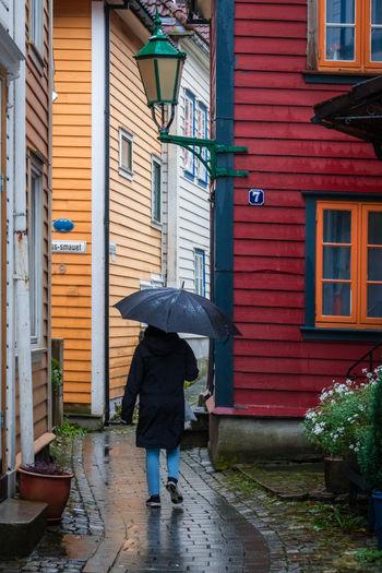 Full length rear view of man walking on footpath in rainy season