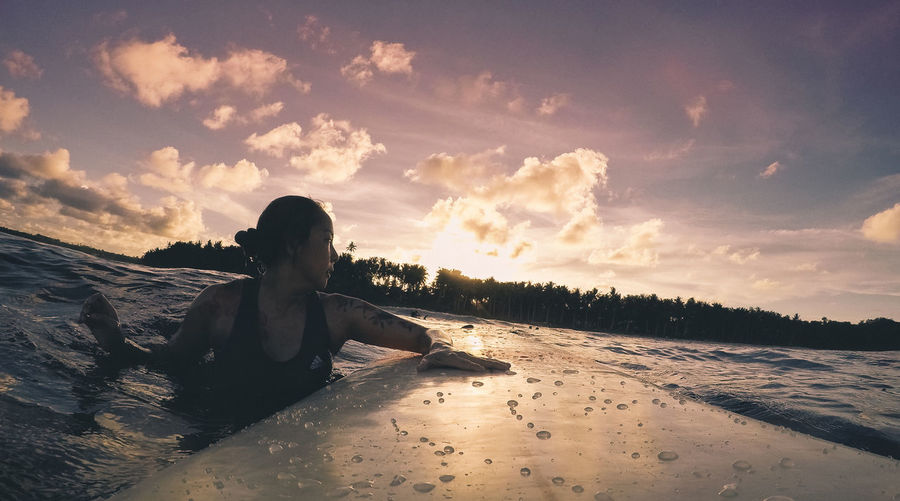 Woman Swimming With Surfboard In Lake Against Sky During Sunset