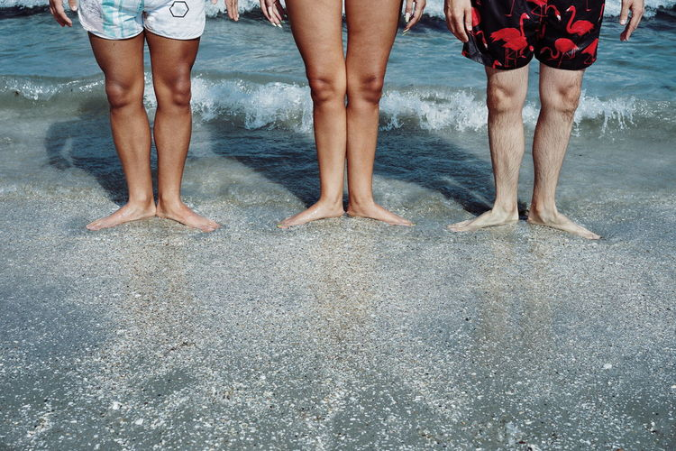 Low section of friends standing at shore