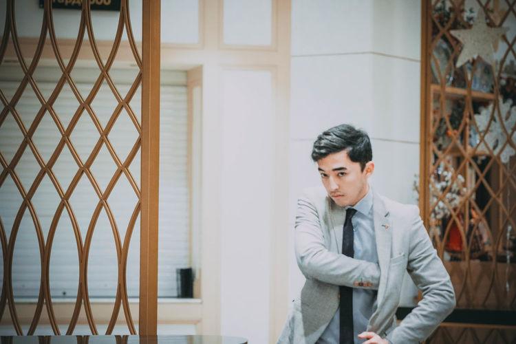 Portrait of businessman standing against house
