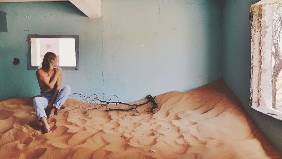 Full Length Of Woman Sitting On Sand In Abandoned Room