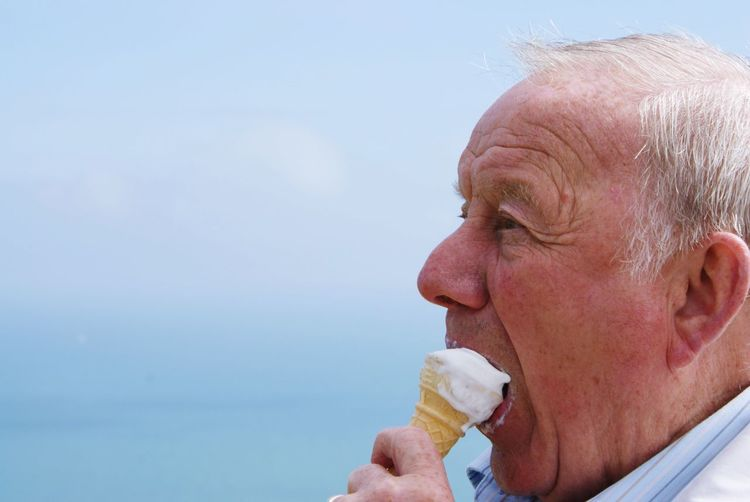 Close-up of man eating ice cream against sky