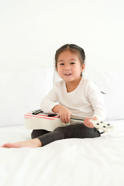 Boys Casual Clothing Child Childhood Children Only Cross-legged Cute Day Elementary Age Full Length Holding Indoors  Learning One Person People Sitting Smiling White Background