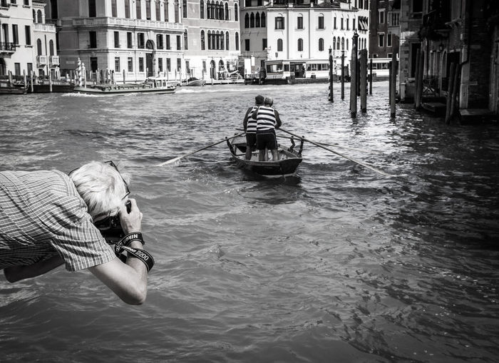Rear view of man photographing on grand canal