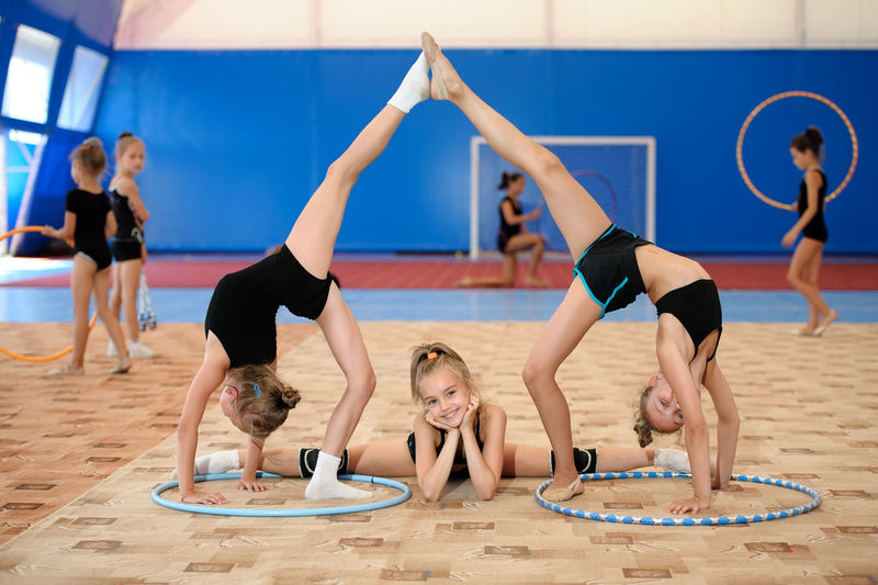 Athlete Caucasian Child Composition Exercise Female Girl Group Gymnast  Gymnastics Hula Hoop Kid Leg-split Pose Position Sport Sportive Sportsman Sportswoman Sporty Stretch