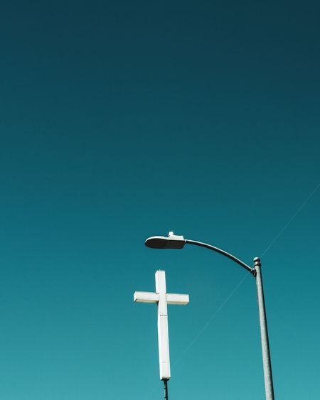 Low angle view of street light and religious cross against clear blue sky