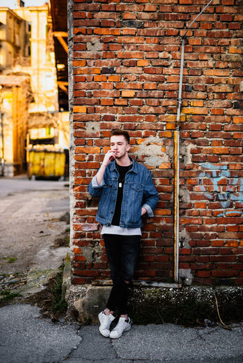 Young man smoking while standing against brick wall