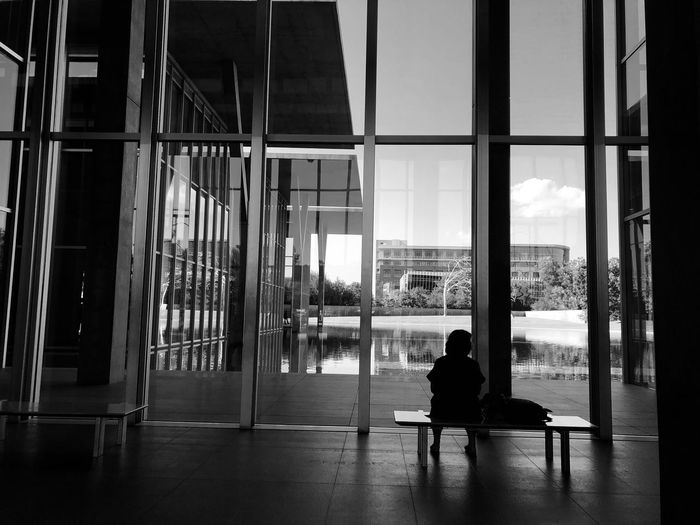 Silent Serenity. Black And White Museum Of Modern Art Architecture Sitting Built Structure Building Exterior Real People Window Rear View Women Leisure Activity Transparent Lifestyles