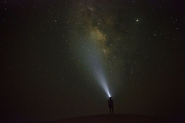 Silhouette of man holding flashlight while standing on land against sky at night