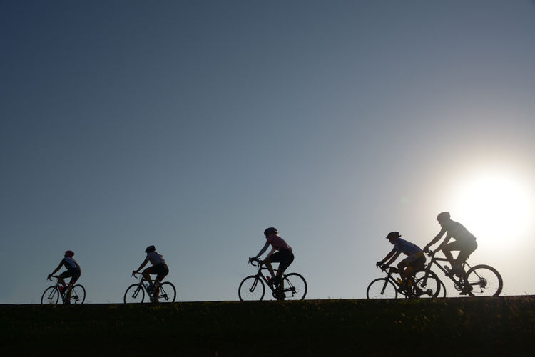 Silhouette people on bicycle against sky