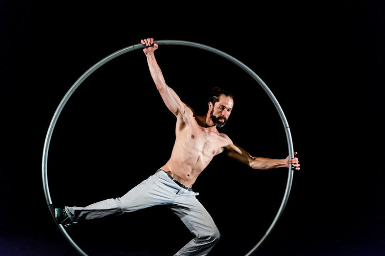 Circus Acrobat Agility Arms Raised Arts Culture And Entertainment Balance Black Background Circus Concentration Expertise Flexibility Full Length Holding Human Arm Indoors  Limb Motion One Person Performance Plastic Hoop Skill  Sport Strength Studio Shot Vitality