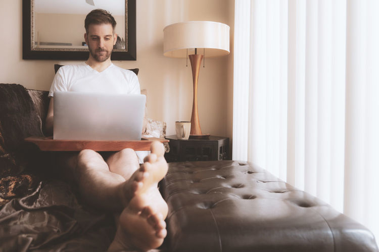 Midsection of man using mobile phone while sitting on bed