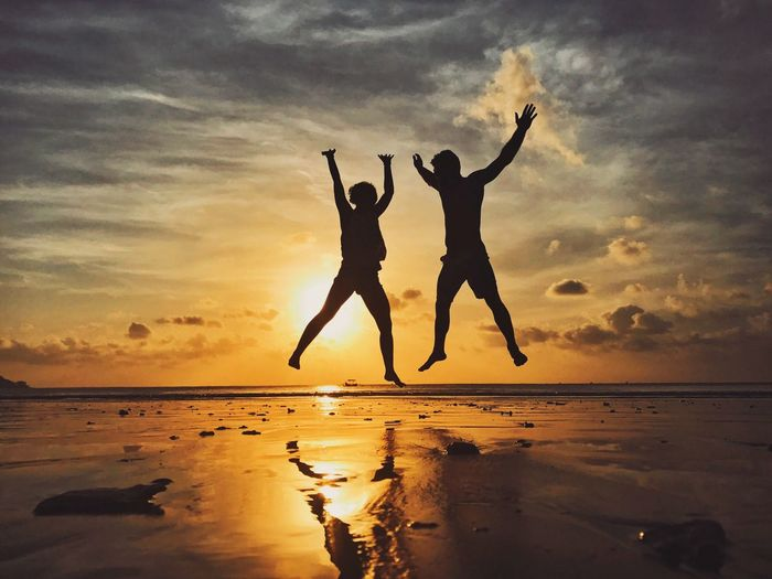 Silhouette couple jumping at beach during sunset