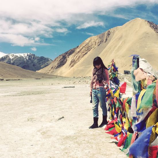 Woman looking down while standing by prayer flags