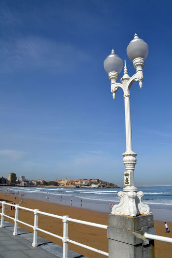 Lighting equipment by beach against sky