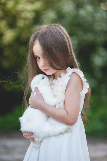 Portrait of girl carrying rabbit while standing against trees