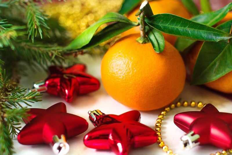 Close-Up Of Christmas Decoration And Orange Fruit On Table