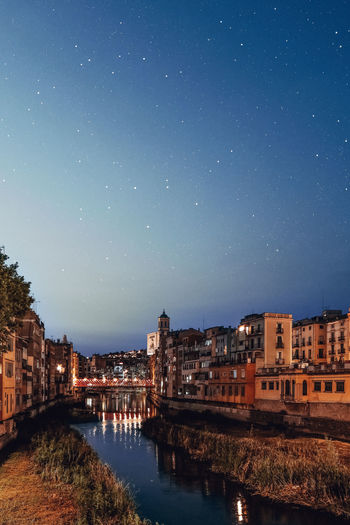 River by illuminated city against sky at night