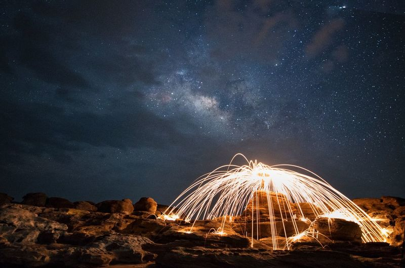 Illuminated wire wool on rock against sky at night