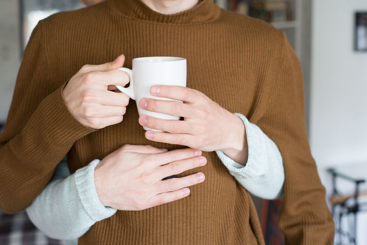 Cropped Hands Of Man Embracing Boyfriend Holding Cup