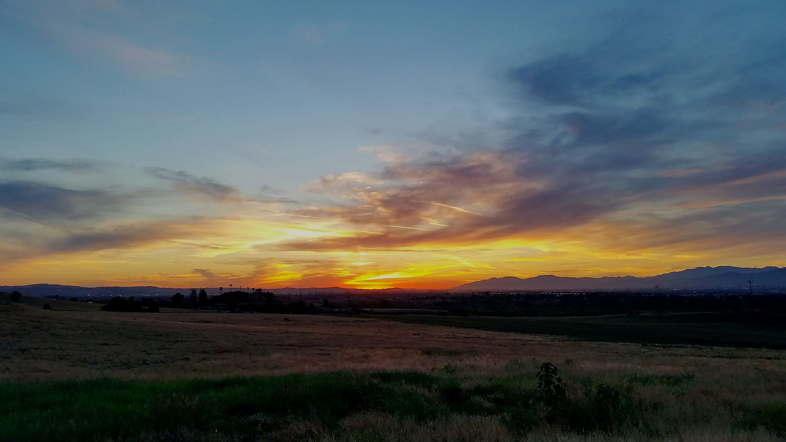 sunset, sky, tranquil scene, scenics, tranquility, cloud - sky, orange color, beauty in nature, landscape, idyllic, water, nature, grass, cloudy, cloud, field, dramatic sky, outdoors, moody sky, non-urban scene