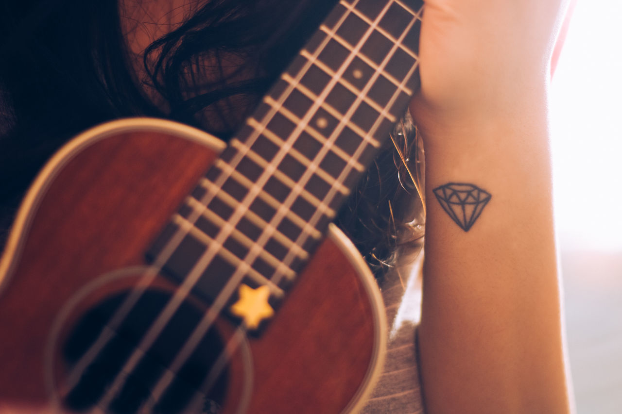 Midsection of woman playing ukulele