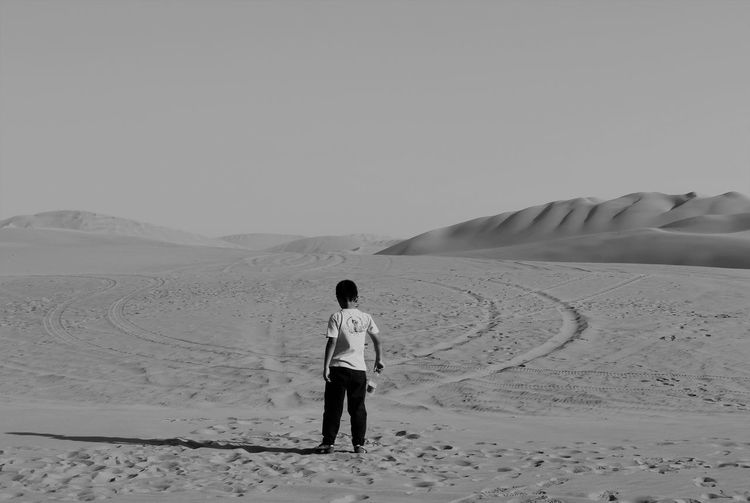 Rear view of boy standing in desert