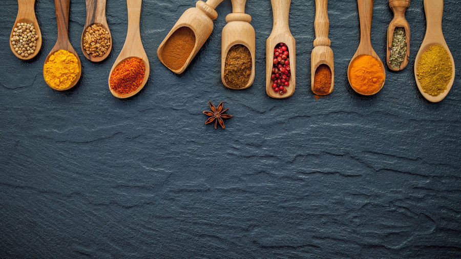 Directly above view of spices in spoons on floor