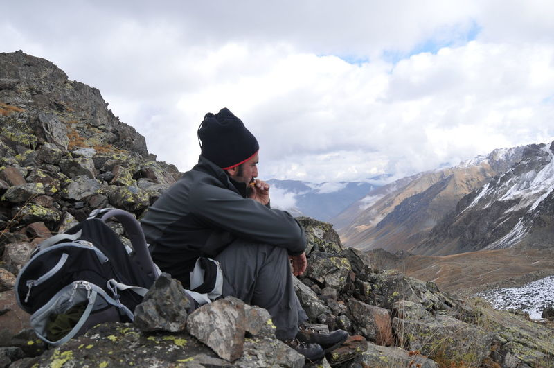 Side view of hiker sitting on mountain against cloudy sky