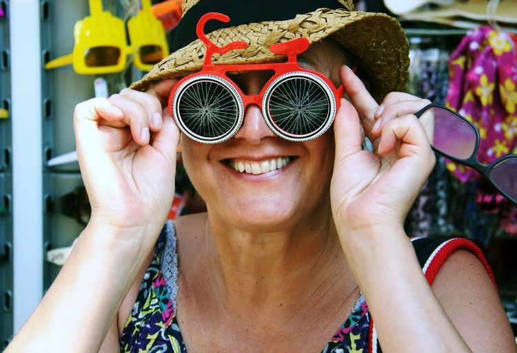Mid adult woman looking through funky sunglasses