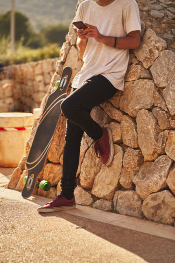 Low section of man holding skateboard on footpath