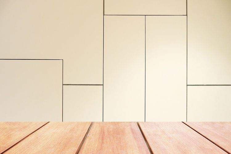 Empty wooden floor against wall at home