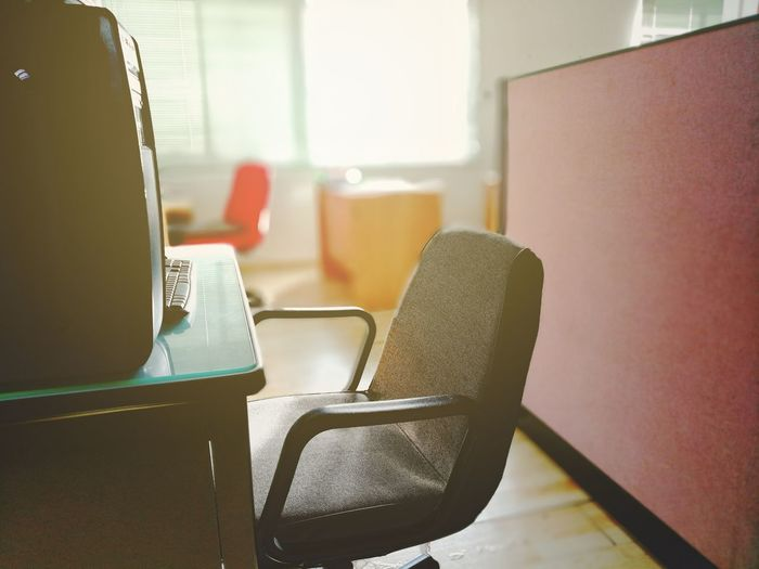 Empty chair at desk in office