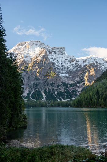 Scenic view of lake by snowcapped mountains against sky