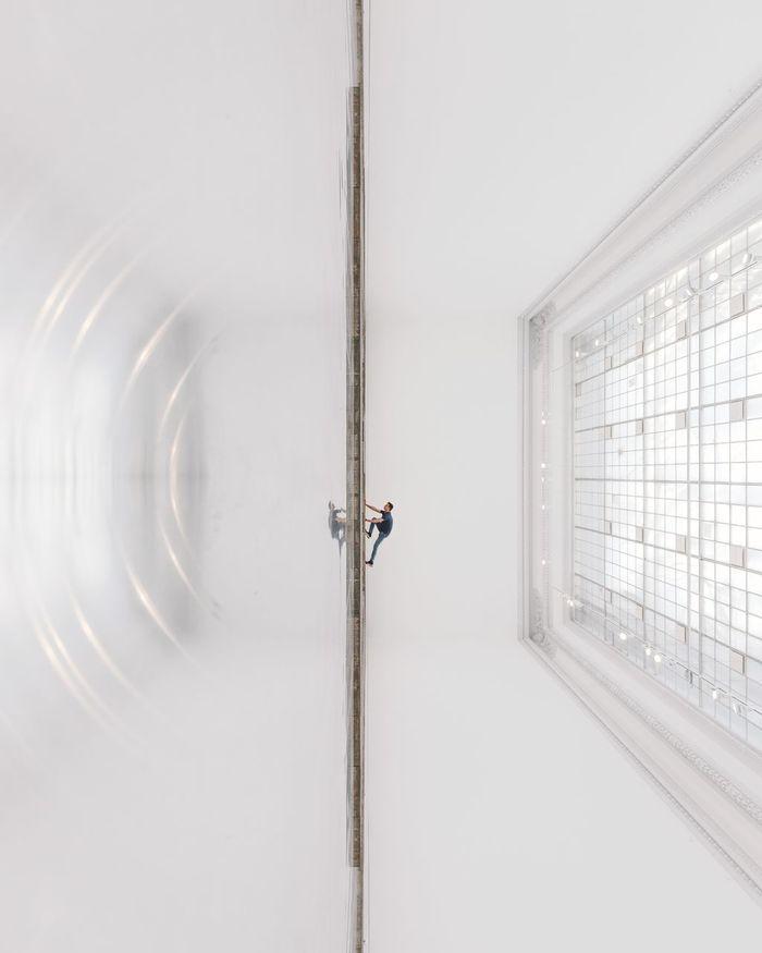 Tilt image of man reflecting on tiled floor